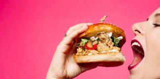 mulher comendo pão de hambúrguer e furando a dieta