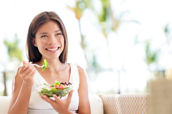 Mulher alimentando-se de salada