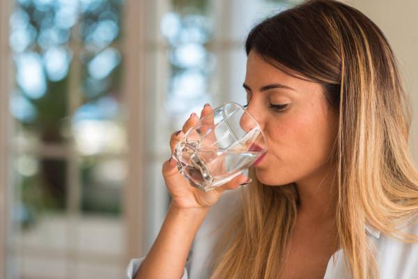 Mulher bebendo água de um copo